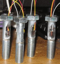 Strain gauged bolts for on-site testing.